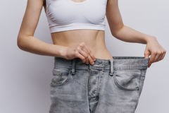 Young beautiful woman on a light background, diet, weight loss, success, progress.  Royalty Free Stock Photos