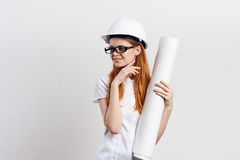 Young beautiful woman on a light background holds blueprints, engineer, work Stock Photography