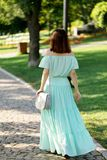 Young beautiful woman in a light green pastel long dress is walk. Ing in the city park in summer. Selective focus royalty free stock photo