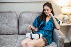 Young beautiful woman in lingerie with gift in hand on sofa.  Royalty Free Stock Images