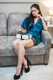 Young beautiful woman in lingerie with gift in hand on sofa.  Royalty Free Stock Image