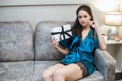 Young beautiful woman in lingerie with gift in hand on sofa.  Royalty Free Stock Photos