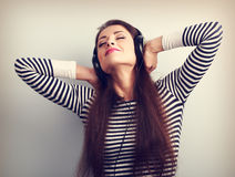Young beautiful woman listening the music from headphones with c Stock Photos
