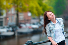 Young beautiful woman listening to music background of canal in Amsterdam, Netherlands Royalty Free Stock Image