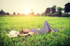 Young beautiful woman listening to music while lying down on gre Stock Image