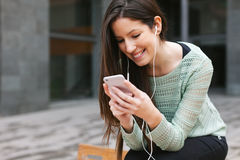 Young beautiful woman listening to music with phone in outdoors. royalty free stock photography