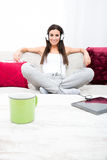Young beautiful woman listening to music with a Tablet PC at hom Royalty Free Stock Image