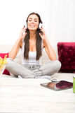 Young beautiful woman listening to music with a Tablet PC at hom Royalty Free Stock Photography