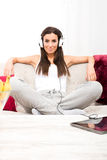 Young beautiful woman listening to music with a Tablet PC at hom Stock Photo