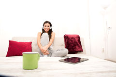 Young beautiful woman listening to music with a Tablet PC at hom Royalty Free Stock Images