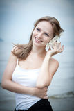 Young beautiful woman  listening  to a seashell Royalty Free Stock Photography