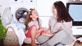 Young beautiful woman and little girl assistant near the washing machine and a heap of laundry for washing. Mom and
