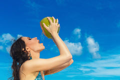 Young beautiful woman with long black hair drinking coconut wate Stock Image