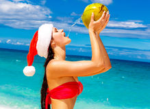 Young beautiful woman with long black hair in red bikini, dresse. D in red Santa Claus hat is drinking coconut water on tropical beach. Christmas and New Year on Royalty Free Stock Photography