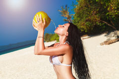 Young beautiful woman with long black hair in white bikini, drin Royalty Free Stock Photo