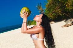 Young beautiful woman with long black hair in white bikini, drin Stock Photography