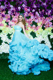 Young beautiful woman with long blond hair in elegant dark blue dress posing at floral background Royalty Free Stock Photos