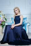Young beautiful woman with long blond hair in elegant dark blue dress posing at white studio. Young beautiful blond woman in dark blue dress posing at white Stock Photo
