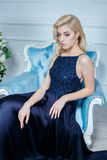 Young beautiful woman with long blond hair in elegant dark blue dress posing at white studio. Young beautiful blond woman in dark blue dress posing at white Royalty Free Stock Photography