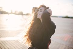 Young beautiful woman with long curly hair dancing and enjoying sunlight stock images