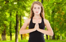 Young beautiful woman with long curly hair meditating in light park background. Hands in namaste. Pray, gratitude, yoga, love God. Concept royalty free stock image