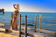 The young beautiful woman in a long dress costs with a white rose in hands on the wooden road over the sea Stock Photo