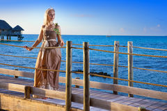 The young beautiful woman in a long dress costs with a white rose in hands on the wooden road over the sea during a sunset Stock Photography