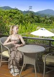 Young beautiful woman in a long dress with a glass of wine looks at the tropical nature. The young beautiful woman in a long dress with a glass of wine looks at Royalty Free Stock Photography