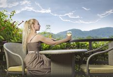 Young beautiful woman in a long dress with a glass of wine looks at the tropical nature. The young beautiful woman in a long dress with a glass of wine looks at Royalty Free Stock Images