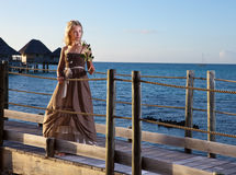 Young beautiful woman in a long dress on the wooden road over the sea Royalty Free Stock Image