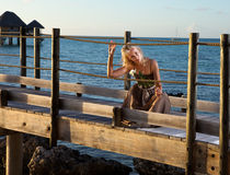 Young beautiful woman in a long dress on the wooden road over the sea Stock Image