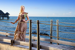 The young beautiful woman in a long dress on the wooden road over the sea Stock Image