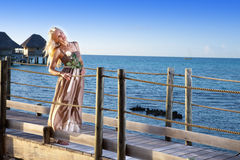 The young beautiful woman in a long dress on the wooden road over the sea Stock Photography