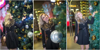 Young beautiful woman with long fair hair outdoor in a cold winter evening. Blonde girl posing near a Xmas tree with Xmas lights Royalty Free Stock Photography