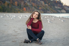 Young beautiful woman with long hair, in black jeans and red shirt, sitting on sand on beach among seagulls birds Stock Photography