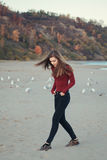Young beautiful woman with long hair, in black jeans and red shirt, sitting on sand on beach among seagulls birds Royalty Free Stock Image