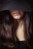 Young beautiful woman with long hair in dark Stock Image
