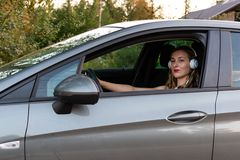 A young, beautiful woman with long hair sits at the wheel of the car. A young, beautiful woman with long hair and headphones sits at the wheel of the car royalty free stock photography