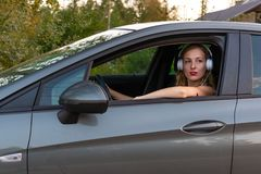 A young, beautiful woman with long hair and headphones sits at the wheel of the car.  stock photos