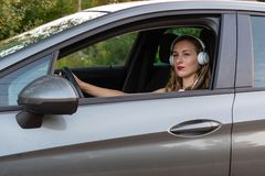 A young, beautiful woman with long hair and headphones sits at the wheel of the car. A young, beautiful woman with long hair and headphones sits at the wheel of royalty free stock photography