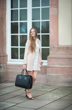 Young beautiful woman with long hair makes cat walk on the street wearing long light pink coat and white dress stock photography