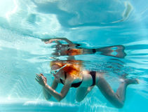 Young beautiful woman with long hair swim in the pool under water. Royalty Free Stock Photos