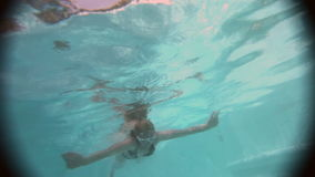The young beautiful woman with long hair swim in the pool under water stock footage