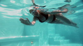 The young beautiful woman with long hair swim in the pool under water stock video footage