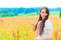 Young beautiful woman with long hair in white in colors Stock Photo