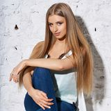 Woman sitting on white chair. Young beautiful woman with long straight blonde hair in blue jeans and bright blouse sitting on white high bar chair with crossed Stock Image