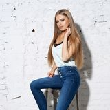 Woman sitting on white chair. Young beautiful woman with long straight blonde hair in blue jeans and bright blouse sitting on white high bar chair with crossed Stock Images