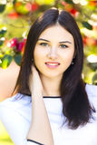 Young beautiful woman with long straight dark hair posing in gar. Den Royalty Free Stock Photo