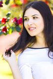 Young beautiful woman with long straight dark hair posing in gar. Den Stock Image