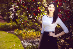 Young beautiful woman with long straight dark hair posing in spr. Ing garden Royalty Free Stock Images